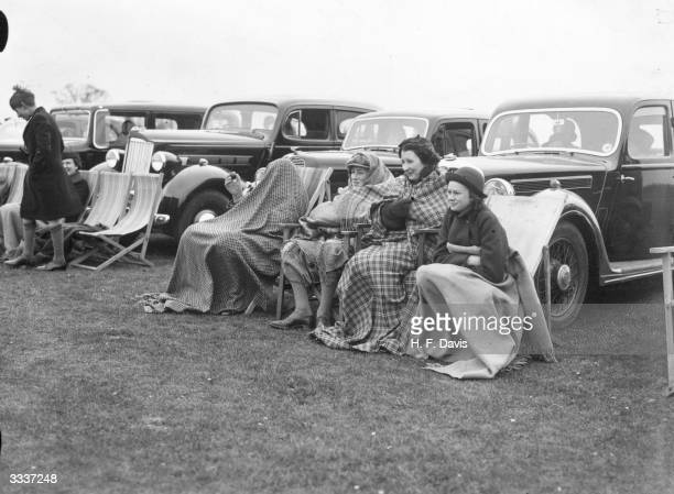 Victor Cubitt Desmond Cubitt Diana Burke and Rowena Burke wrap up against the cold whilst watching the Polo match between kent and Sussex at...