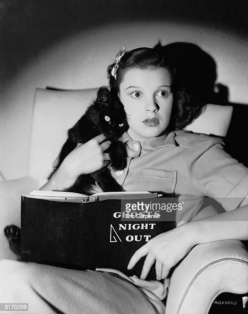 Cuddling a black cat a scared looking Judy Garland is reading a book 'Ghost's Night Out'