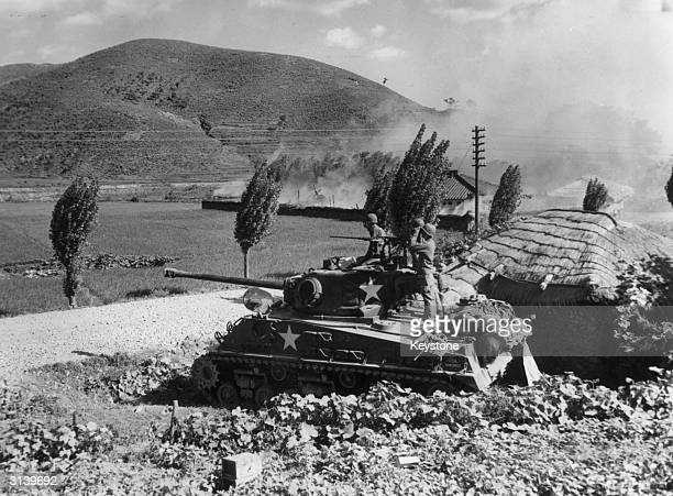An American Army tank firing on enemy positions in the area around Masan in Korea