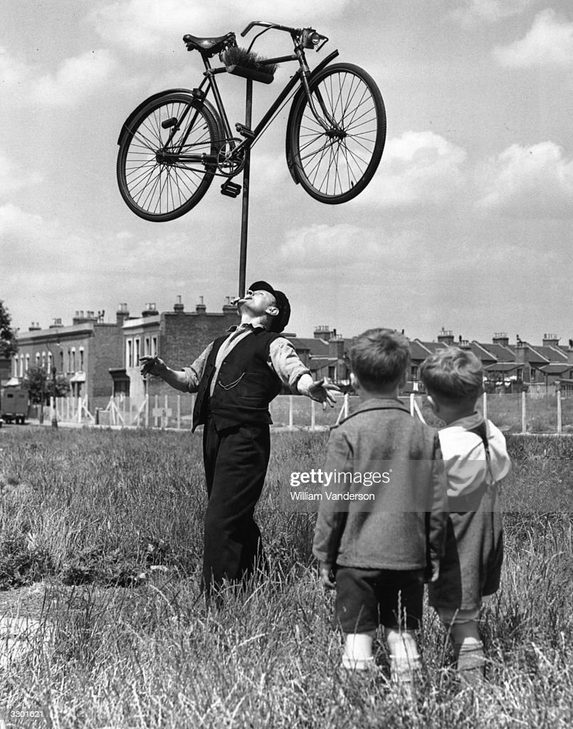 In the field outside his house in Plaistow, East London, 62-year-old railway worker Mo Harris balances a bicycle on top of a broom on his chin, watched by a couple of incredulous youngsters. Harris is known as 'the chin-up boy of Stratford'.