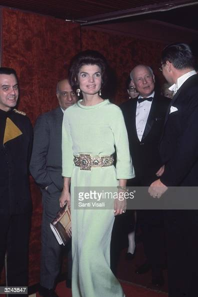 EXCLUSIVE Jacqueline Kennedy stands and holds a program while attending the Metropolitan Opera Lincoln Center New York City She wears a long white...