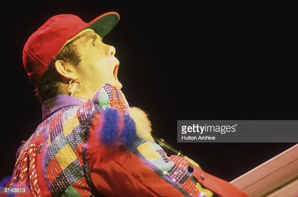 English pop star Elton John performing in a colourful costume at the Hammersmith Odeon