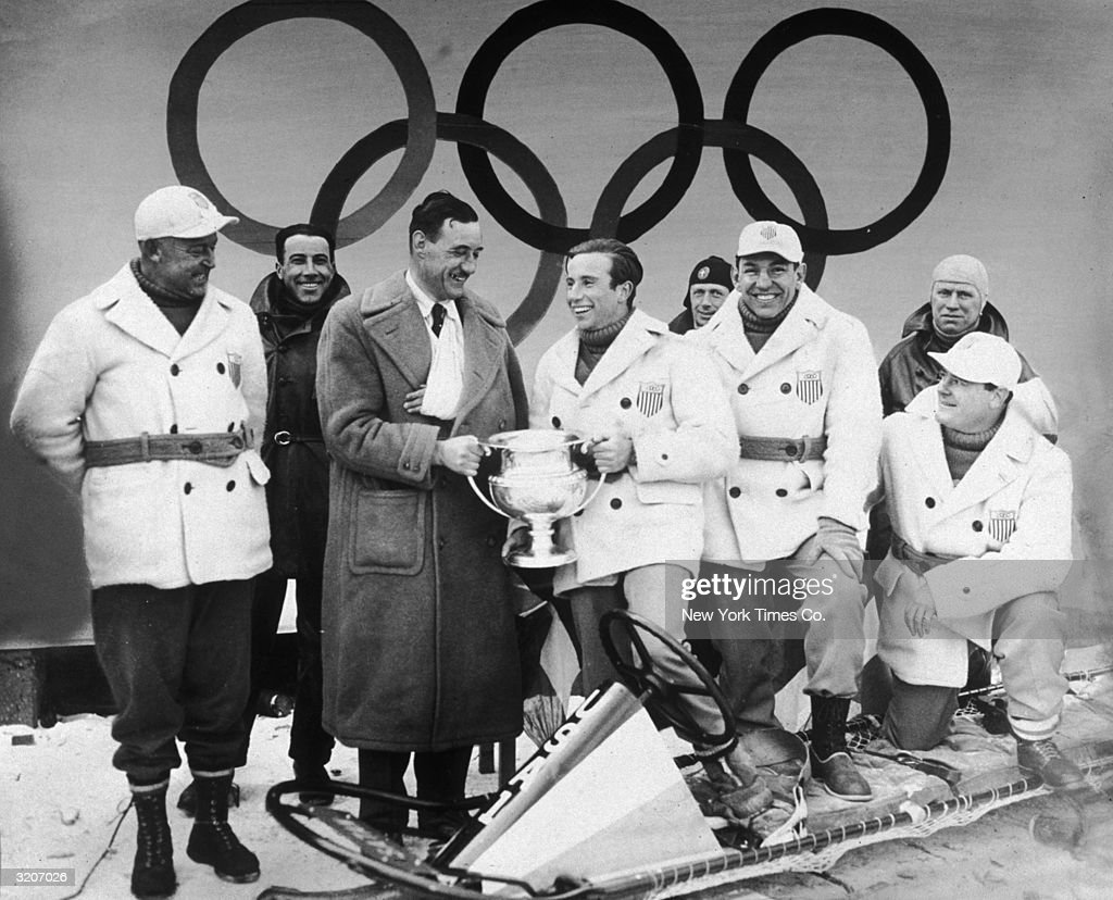 Portrait of German bobsledder Werner Zahn presenting the Olympic trophy to American bobsledder William L Fiske while the rest of the fourman winning...