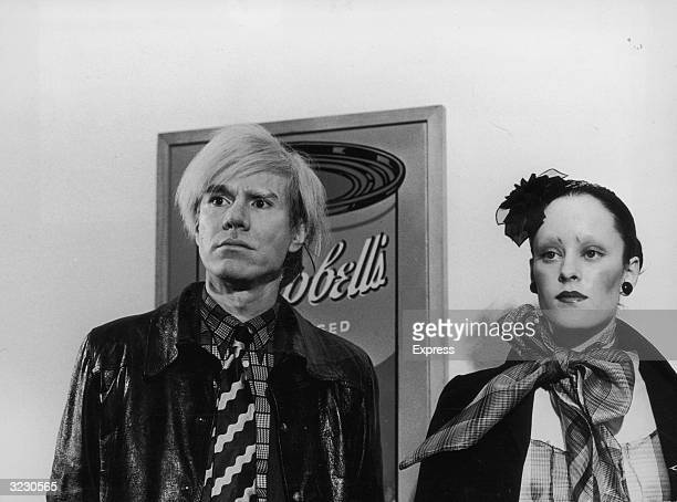 American Pop artist Andy Warhol stands next to actress Jane Forth star of his new film 'Trash' in front of his famous Campbell's Soup painting in...
