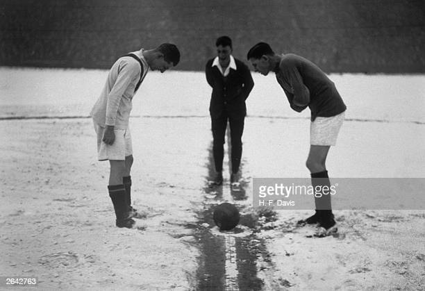The referee tosses up on a snowcovered football pitch at the start of the football match between Arsenal and Manchester United at Highbury