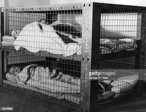 A group of men in the new twotier Morrison shelter similar in construction to the original indoor shelter but housing two beds one above the other...