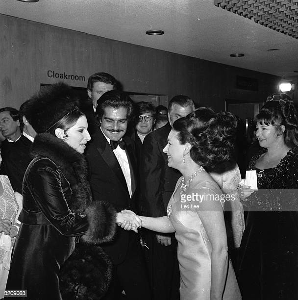 Barbra Streisand shaking hands with Princess Margaret at the European premiere of William Wyler's film 'Funny Girl' Her costar Omar Sharif looks on