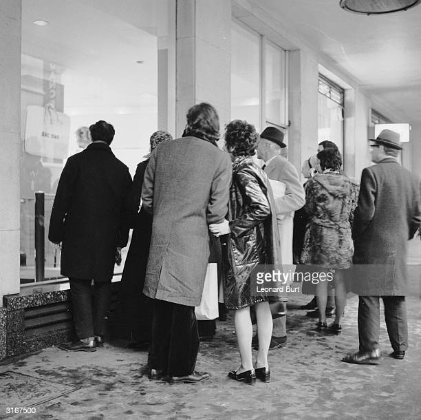 Londoners peer through the windows of an art gallery in New Bond Street after officers from the Obscene Publications department of Scotland Yard...