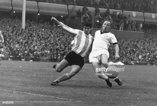 Argentinian centre half Jorge Albrecht tackles West German centre forward Uwe Seeler after he shoots for the goal during a World Cup match at Villa...