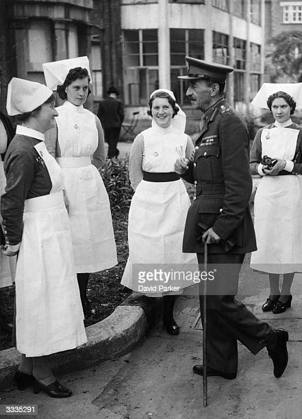 Brigadier General Whitehead Officer in Charge of the London Home Guards chats with some nurses at a garden party at the Mile End Hospital East London...
