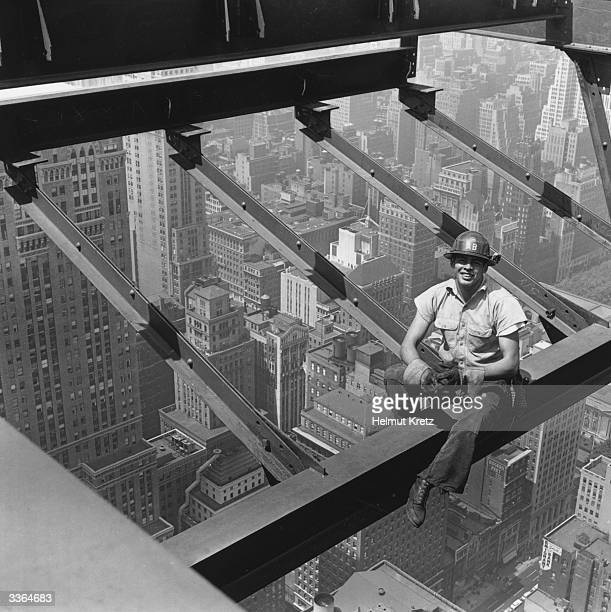 A construction worker on the Pan American building sits on a girder above the New York streets