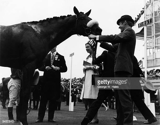 Queen Elizabeth II talking to Geoff Lewis the jockey of a sweaty 'Magna Carta' in the unsaddling enclosure after he had won the Ascot Stakes On the...