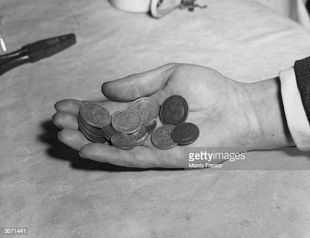 A hand holding British loose change including a half crown and a two shilling coin