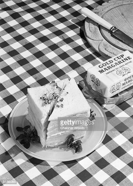 A pile of sandwiches with their crusts trimmed off and a packet of margarine on a check tablecloth Eldorado