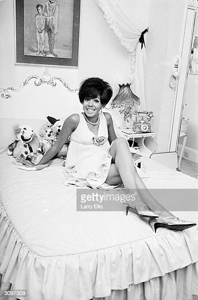 Welsh singer Shirley Bassey sitting on her bed