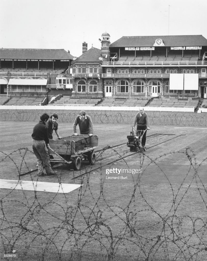 Ground staff at work on the artificial pitch at the Oval surrounded by barbed wire which has been erected temporarily to stop antiapartheid...