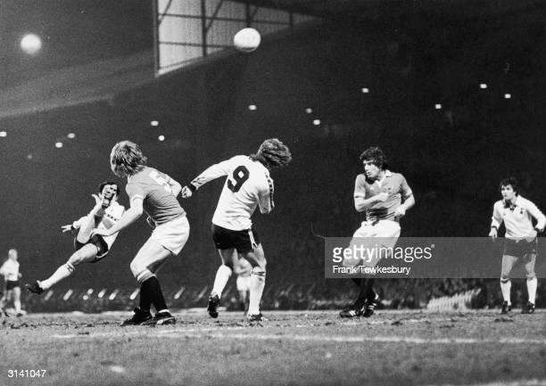 Manchester United footballers Gordon McQueen and Martin Buchan watch as the Tottenham Hotspur player Osvaldo Ardiles attempts an overhead kick