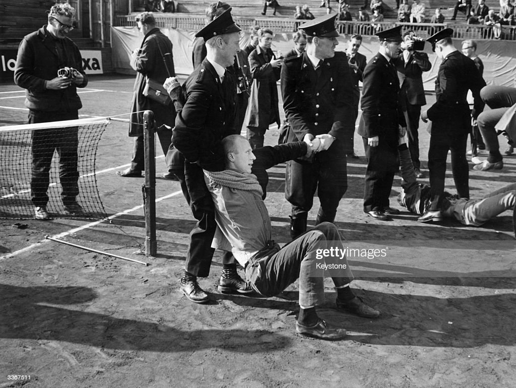 A man being arrested at an antiapartheid demonstration in Oslo which involved sitting down on the tennis court to stop a Davis cup match against a...