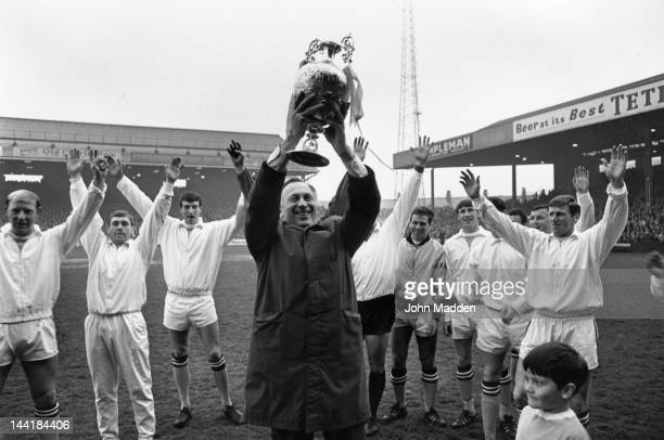 Manchester City Manager Joe Mercer holds the League Championship trophy aloft after an exhibition match against Bury at Maine Road Manchester