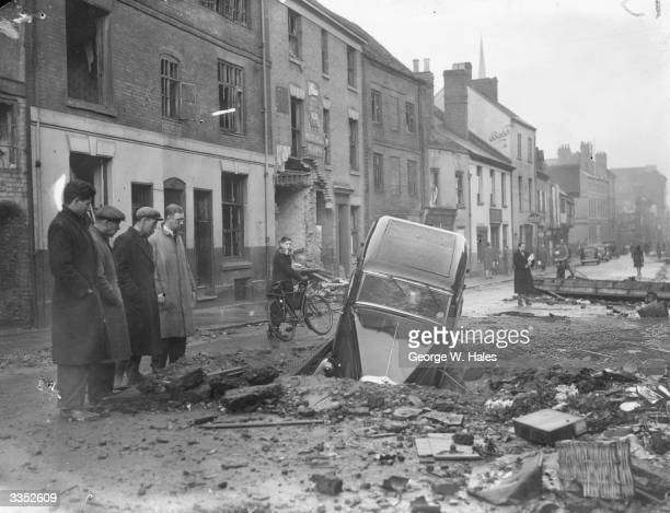 A car in a bomb crater on a Coventry street following a nighttime air raid by German planes