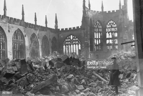 A man stands in the ruins of Coventry Cathedral after a German nighttime airraid destroyed the centre of the city