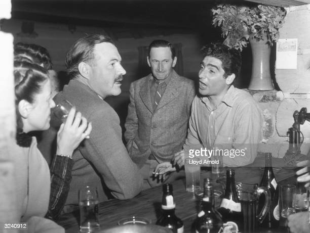 EXCLUSIVE Hungarianborn photojournalist Robert Capa talks to American writer Ernest Hemingway while standing at a bar at Trail Creek Cabin Ketchum...