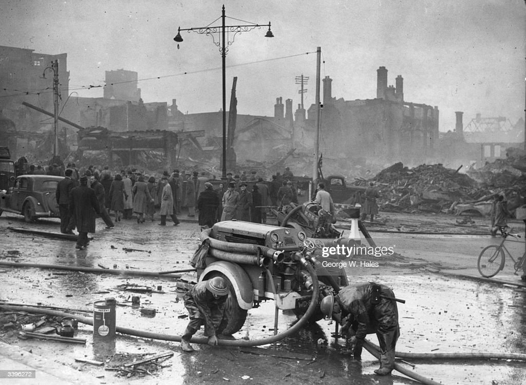 Firemen attend the pumps in Coventry as daybreak reveals the devastation wreaked by Luftwaffe bombers during the nightly air raids on the city.