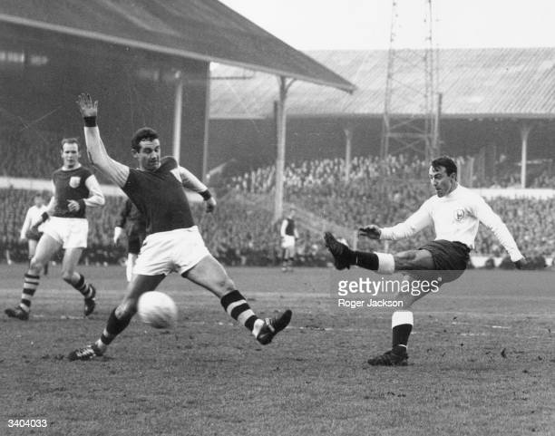 Tottenham Hotspur's Jimmy Greaves has a shot at goal blocked by Burnley defender Joyce during a match at White Hart Lane