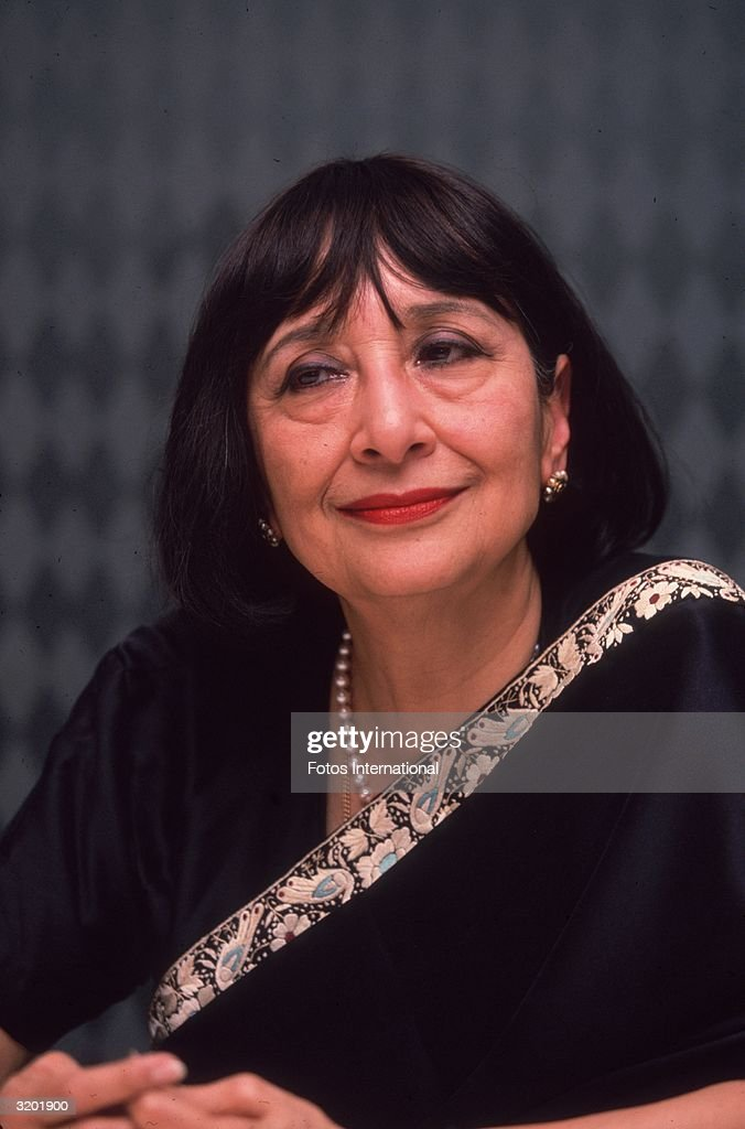 Headshot studio portrait of Indian actor Madhur Jaffrey wearing a sari, smiling while seated in front of a black and white diagonally checkered backdrop, Beverly Hills, California.