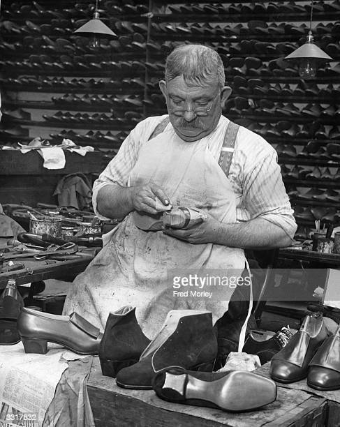 A man works on a pair of shoes with scoopedout heels for actress Marlene Dietrich at a Northampton factory