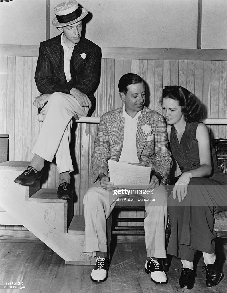 Composer Cole Porter (1891 - 1964) discusses his musical score with dancers Fred Astaire (1899 - 1987) and Eleanor Powell (1912 - 1982) on the set of 'Broadway Melody of 1940', directed by Norman Taurog.