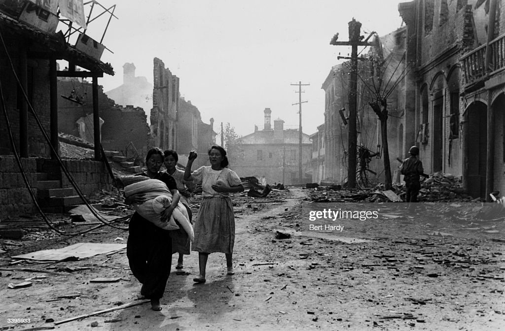 Korean refugees threading their way through the bomb devastated streets of Inchon after an American attack on the port Original Publication Picture...