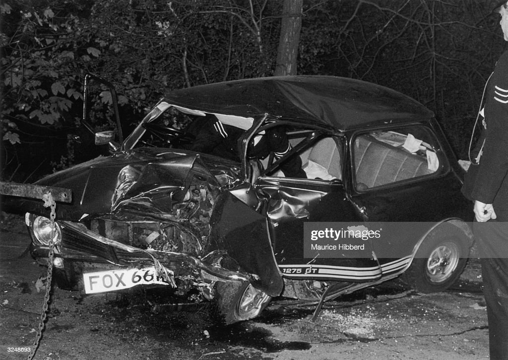 A policeman examines the wrecked Mini 1275 GT in which pop singer Marc Bolan (1947 - 1977) died when it collided with a tree on Barnes Common, London. Bolan's girlfriend, Gloria Jones who had been driving, survived with serious injuries.