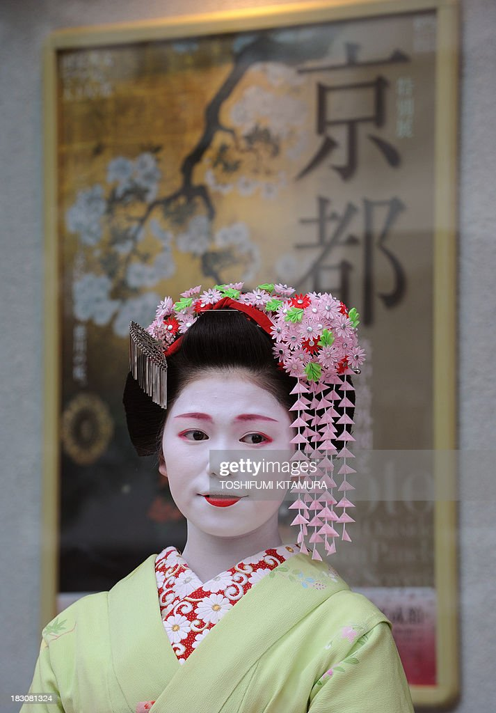 16-year-old Toshitomo, a 'Maiko,' or apprentice geisha, from Miyagawa cho attends the 'We're alive and well, Kyoto' campaign in Tokyo on October 4, 2013. As Kyoto prepares itself for the biggest sightseeing season of autumn, the girls lent their charms to lure back tourists to the 1,200-year-old city after a big typhoon flooded some of scenic spots there three weeks ago. AFP PHOTO / TOSHIFUMI KITAMURA
