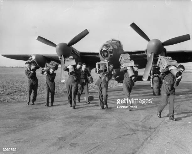 Airmen of the Photographic Reconnaissance branch of the Royal Airforce unloading giant cameras from one of the Mosquito planes at the Central...