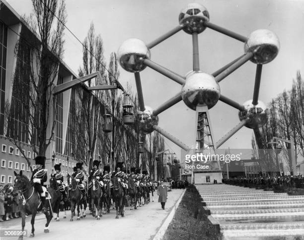 Mounted soldiers make a royal escort for King Baudouin of the Belgians at the opening of the Brussels Exhibition The Atomium is in the background