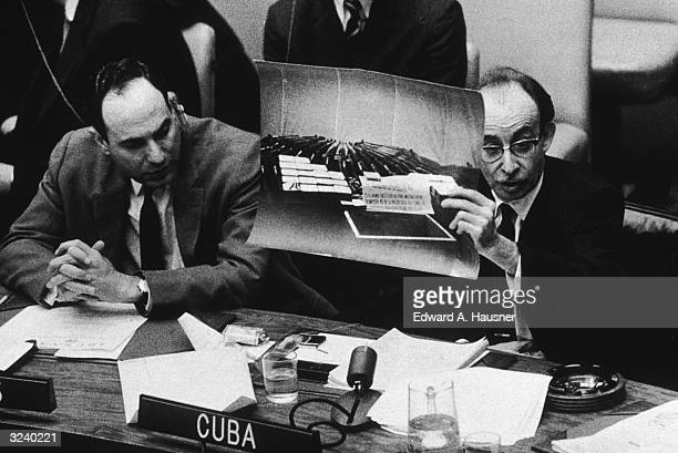 Cuban foreign minister Raoul Roa shows UN delegates photographs of arms he said were supplied by the United States for the Bay of Pigs Invasion...