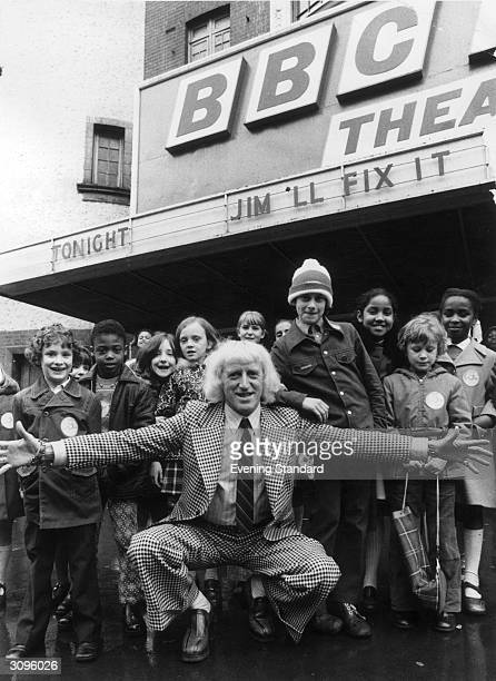English radio disc jockey television broadcaster and charity worker Jimmy Savile with some of the children who will be taking part in his new series...
