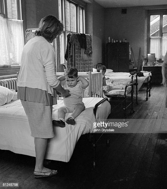 17th August 1962 Mrs Victor Moore gets her small son ready for bed in the shared dormitory at Luxborough Lodge a London County Council accomodation...