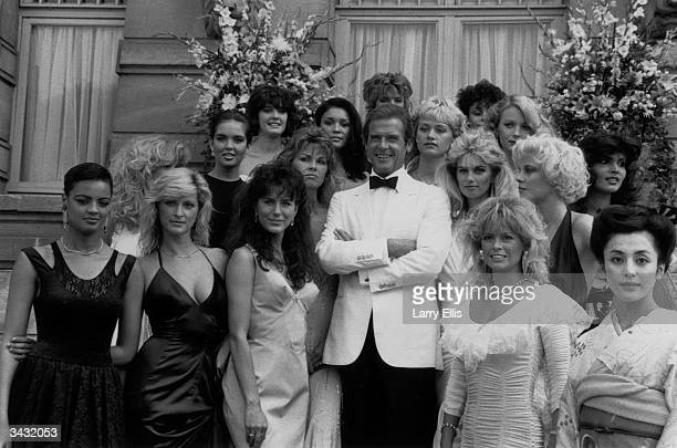 Film star Roger Moore and the Bond Girls from the film 'View to a Kill' directed by John Glen