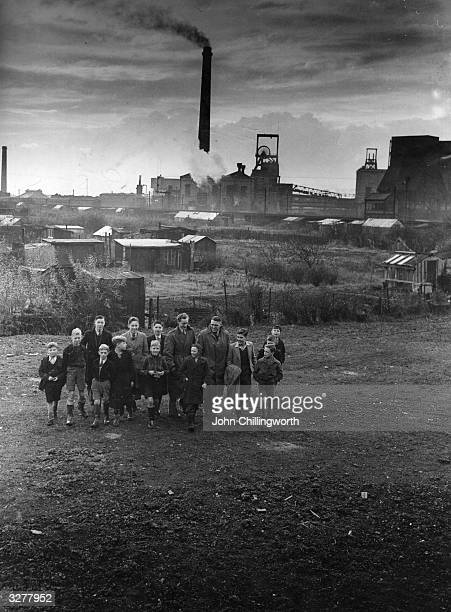 A group of young supporters accompany Rugby League players Bill Kingdon and Cec Ryan across allotments to the Kirkhall Lane rugby ground in Leigh...