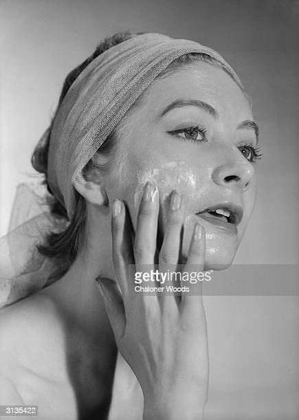 A woman her hair tied back with a bandeau applies cream to her face