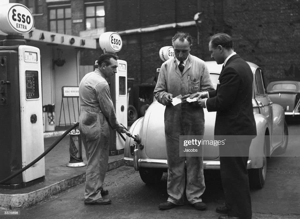 A garage worker taking petrol coupons as another fills a customer's car on the first day of petrol rationing.