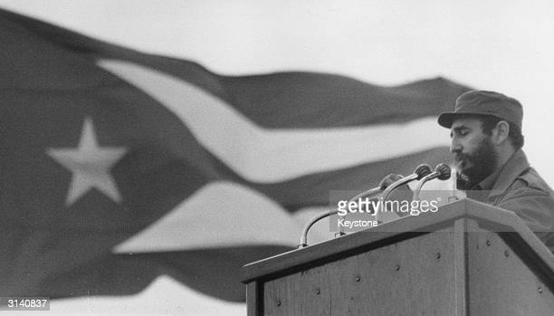 Fidel Castro giving a speech with the national flag of Cuba in the background