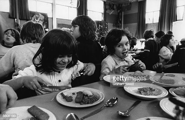 Young pupils at Edith Neville School North London enjoy their school dinner of fish fingers baked beans and potato with sponge and custard to follow
