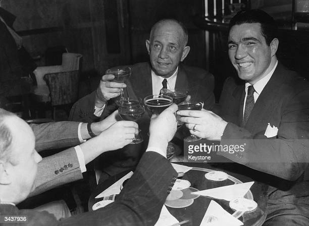 American boxer Joey Maxim and his manager 'Doc' Hearns being toasted by sports writers upon their arrival in New York after Maxim won the World...