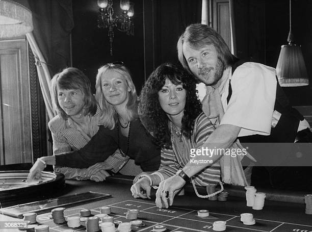Swedish pop group ABBA try their luck at a Crockford's roulette table whilst attending the premiere of their latest film 'ABBA The Movie' in London...