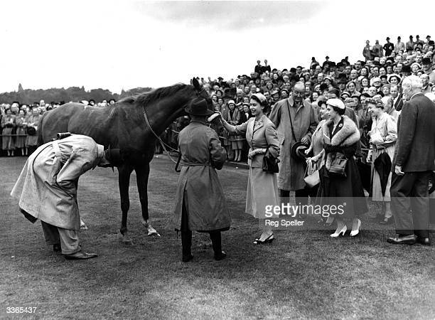 Queen Elizabeth II patting her horse Aureole after it came in first at the Royal Ascot race meeting on Ascot Heath Berkshire Princess Margaret Rose...