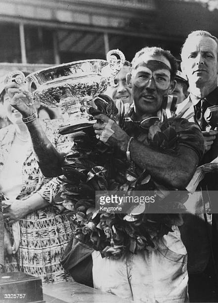 English motorracing driver Stirling Moss the winner's laurels around his neck holds up the Grand Prix Cup after winning the British Grand Prix at the...
