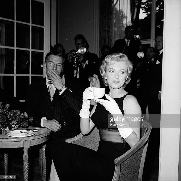 American film star Marilyn Monroe sits next to British thespian Laurence Olivier at a press conference at the Savoy Hotel London